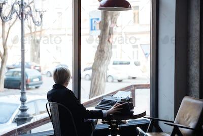 Blonde girl sitting backwards in a cafe