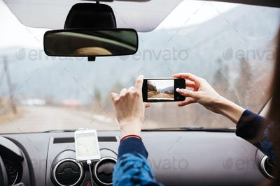 Woman hands driving and taking photos with mobile phone