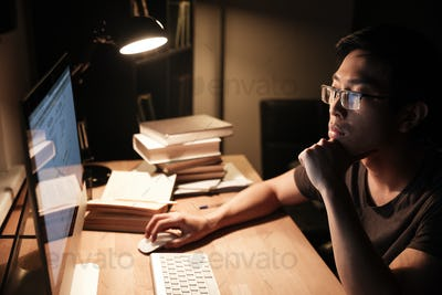 Pensive man working with computer and thinking in the evening
