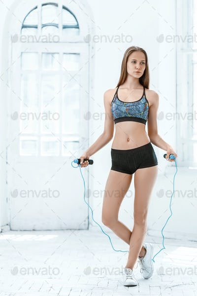 Muscular young woman athlete with a skipping rope on white