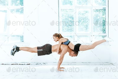The fit woman and man doing some push ups at the gym