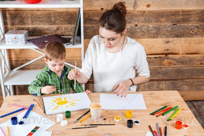 Mother and little son painting sun together