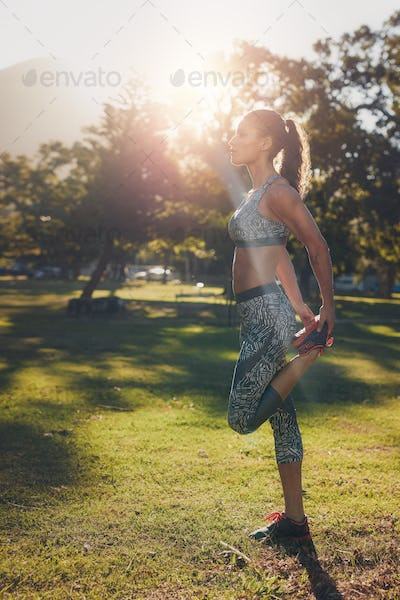 Runner athlete stretching legs outdoors in a park