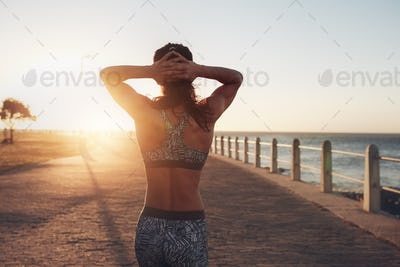 Sportswoman taking a walk by the sea at sunset
