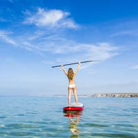 A beautiful and happy woman with arms up and learning paddle-sur