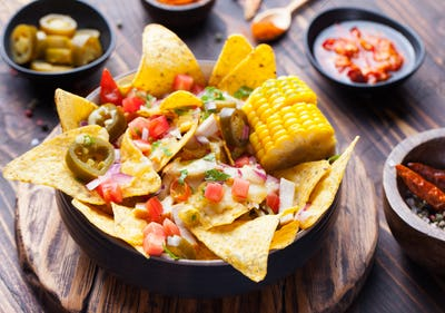 Nachos with melted cheese sauce, salsa, corn cobs
