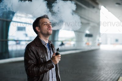 Young traveller man smoking an electronic cigarette outdoor near the airport terminal