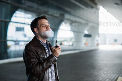 Young man enjoying a satisfying e-cigarette standing in profile against airport terminal background