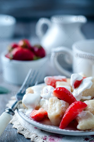 Cottage cheese dumplings with strawberries on background top view