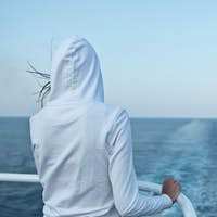 Young woman looking at the ocean from a fast going liner