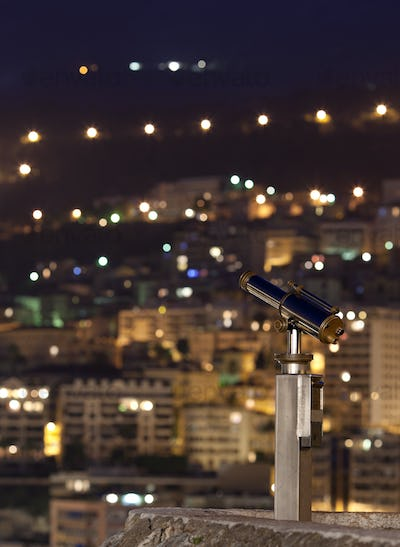 night city (with a telescope in the foreground, focus is on the