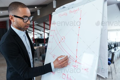 Businessman writing something on the flipchart