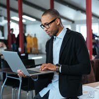 Serious businessman is standing and using laptop