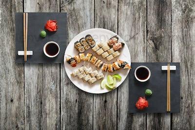 Set of sushi maki and rolls at black rustic wood.