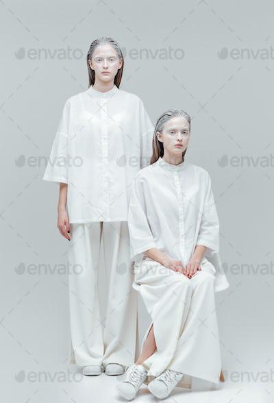 Two beautiful mystical women in white dress