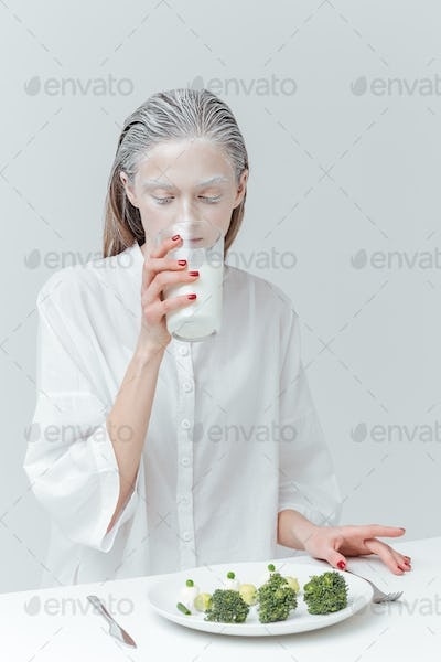 Girl drinking milk and having lunch at the table