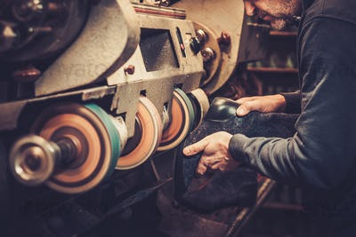 Shoemaker performs shoes in the studio craft grinder machine.
