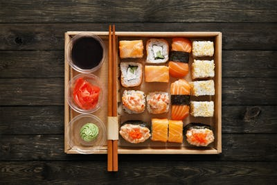 Set of sushi maki and rolls at box on wood.