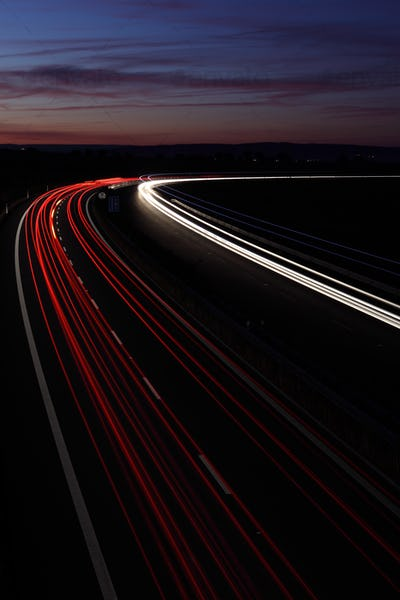 Cars in a rush moving fast on a highway (speedway) at dusk