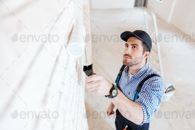 Close-up portrait of a decorator using roller during work