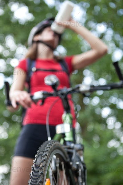 pretty young female biker outddors on her mountain bike (shallow