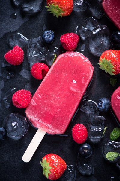 Refreshing popsicle on ice cubes and fruits