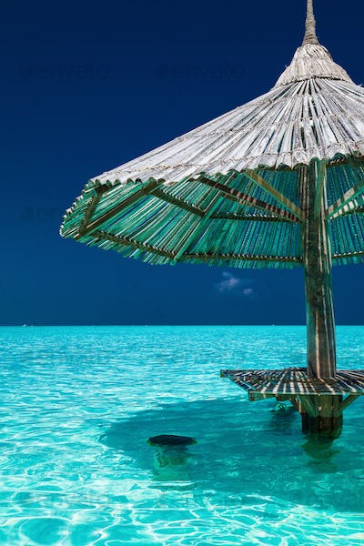 Bamboo beach umbrella in the water of tropical island