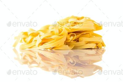 Yellow Tagliatelle Taglionlini pasta on white background