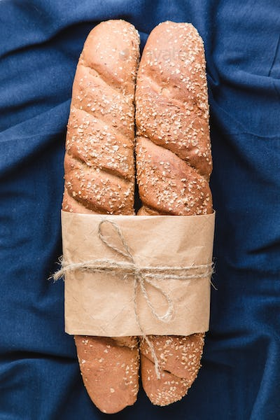Two French baguettes with on blue textile