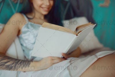 Beautiful smiling excited woman reading a book in the morning