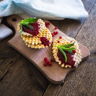 Waffle with berry jam, powdered sugar and mint on black background