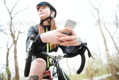 Pensive woman on bike using mobile phone in park