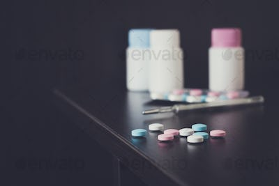 colorful pills and thermometer on brown table
