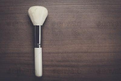 white make-up brush on brown table