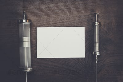 retro medical syringes and notebook on wooden background