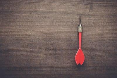 red dart on wooden background