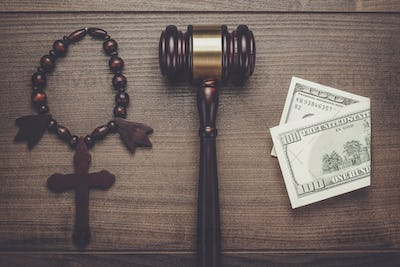 wooden cross gavel and money on brown table background