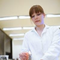 pretty female researcher/chemistry student lighting up a burner