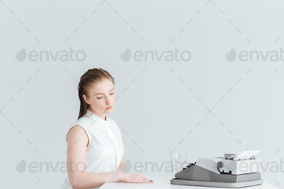 Woman sitting at the table with retro machine