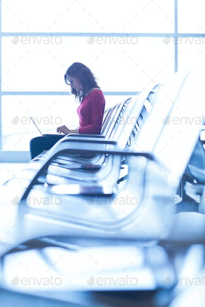 Young woman at the airport, working on a laptop and waiting for