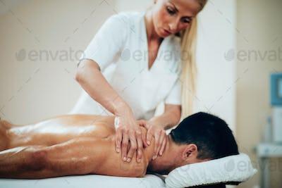 Sports massage. Therapist doing shoulder massage