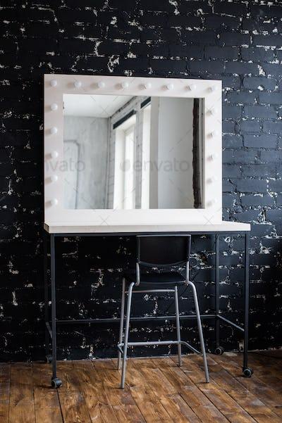 Woman's makeup place with mirror and bulbs at photo studio loft interior black brick wall