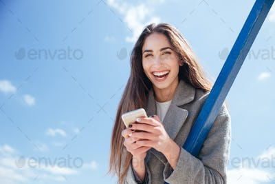 Young smiling beautiful woman holding camera outdoors