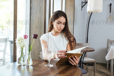 Beautiful young woman in a restaurant reading menu