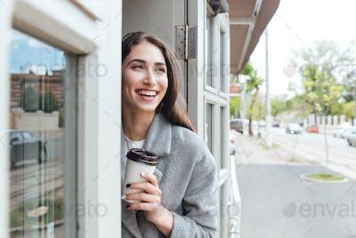 Happy cheerful smiling girl holding take away coffee