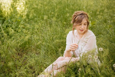 Charming sensual young woman sitting on grass with dandelions