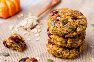 Pumpkin, oat cookies with cranberries and maple glaze on a rustic textile background