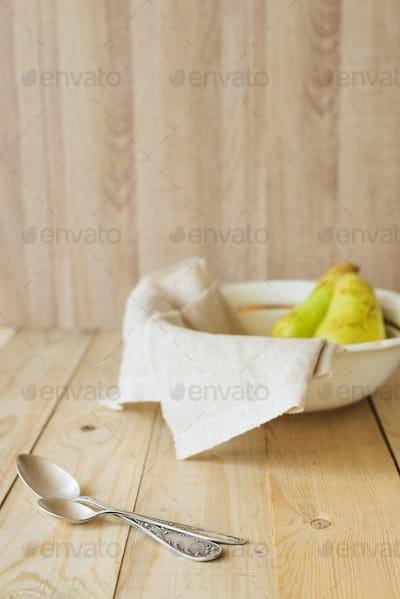 two tablespoons on background of pears in bowl