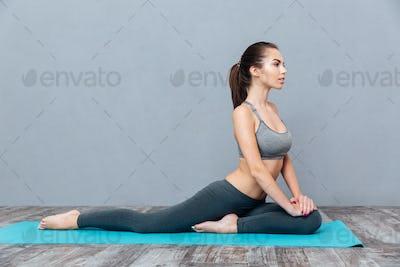Young smiling girl in sportswear sitting on splits