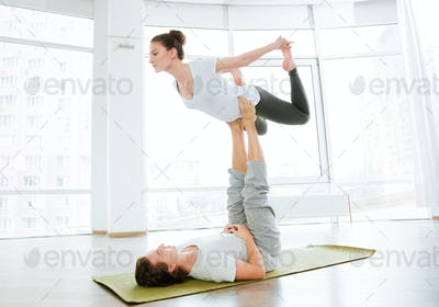 Beautiful couple balancing and doing acro yoga